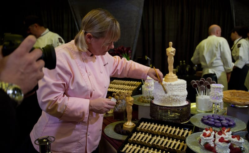 Sherry Yard dusting the Oscars cake with gold